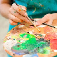 Image of hands holding a paint palette and brush.